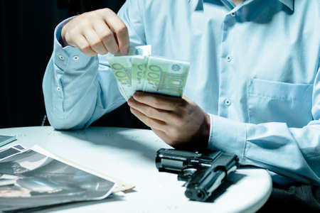 Cropped picture of a man counting money and holding his hands on a table with a gun