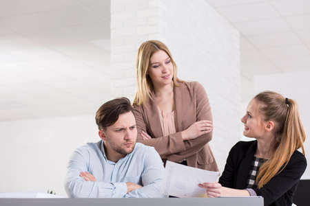 team working: Young woman describing her ideas to her work mates Stock Photo