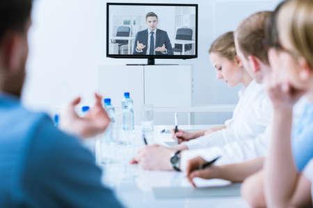 Video conferencia médica en una sala de conferencias brillante, borroso, con una pantalla de televisión en el medio Foto de archivo - 60370742