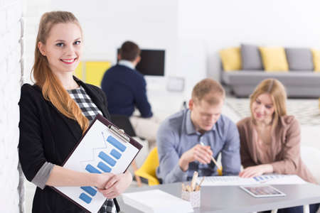 style advice: Smiled woman with reports standing in the open space area with other workers behind