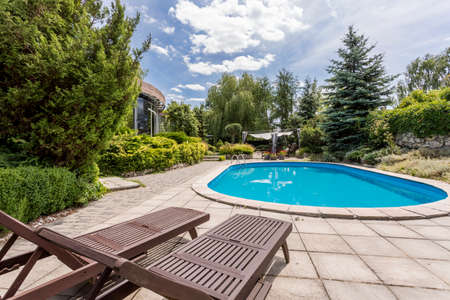 luxurious: Oval swimming pool and two deckchairs in a large garden of a modern house