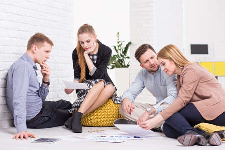 mates: Work mates sitting on a floor and discussing the project details Stock Photo