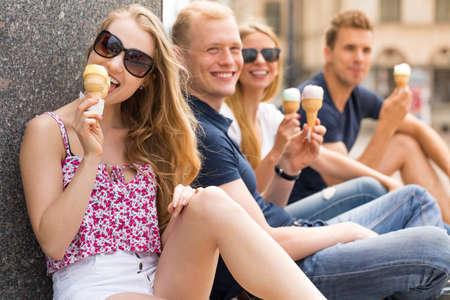 comiendo helado: Recortar foto de una mujer hermosa que come el helado con sus amigos en el fondo