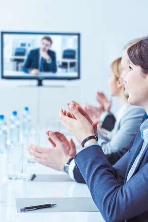 manos aplaudiendo: Los miembros de la rueda de negocios aplaudiendo y sonriendo en una sala de conferencias Foto de archivo