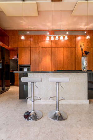 fronts: Stylish kitchen with dark wood cabinet fronts, black fridge and marble floor