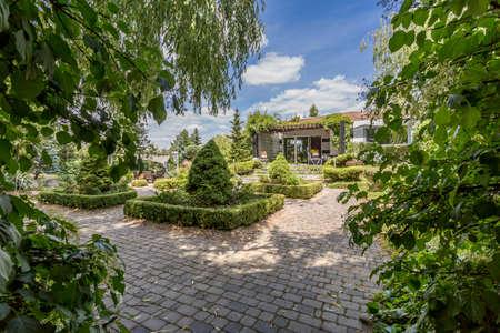 empedrado: Jardín muy grande con las vías de pavimiento, y una vivienda unifamiliar en el fondo Foto de archivo