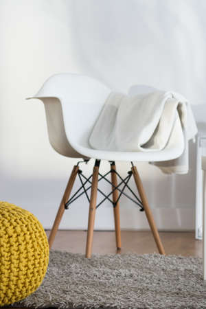 cropped shot: Cropped shot of a modern armchair standing in a living room designed in white