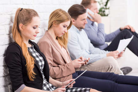 style advice: Young workers sitting leaned on the wall and concentrated on their tasks Stock Photo