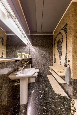 granite floor: Extravagant dark bathroom with granite floor and mosaic wall