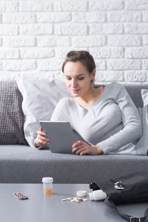 sick leave: Young woman on sick leave browsing internet on the couch