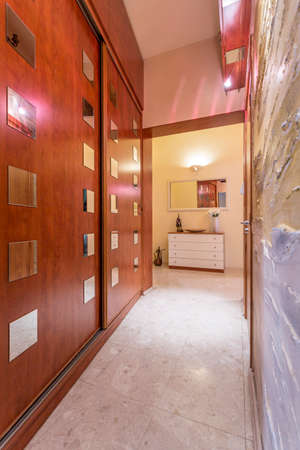 sliding doors: Massive wardrobe sliding doors with decorations of mirror tiles, in a marble hallway