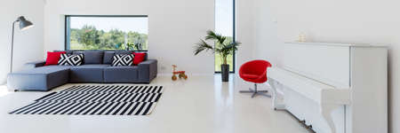 comfort: White interior of a living room with a piano, couch with cushions, lamp, red armchair and striped carpet