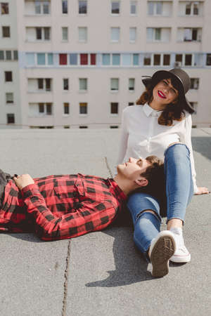 allegiance: Young man lying on a roof with his head on legs of young woman in hat sitting close