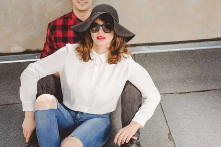 leaned: Young hipster couple with the woman with a hat and sunglasses sitting leaned on mans chest Stock Photo