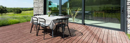 hause: Closer shot of a table and chairs standing at an open area of hause terrace in s sunny day, close to the window Stock Photo
