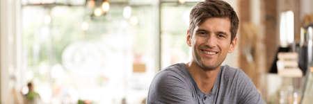 portrait positif d'un jeune homme assis à la barre d'un café floue
