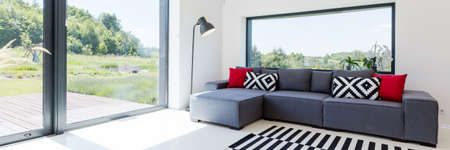 White interior of a living room with large couch with cushions, lamp, striped carpet and glazed patio entry