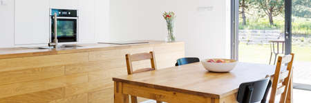 Dining room with an open plan kitchen area with wooden table, chairs, wide table top and patio entry