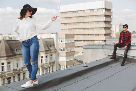 allegiance: Young woman in modern clothes with a hat, posing on a roof with a man in checked shirt at the background