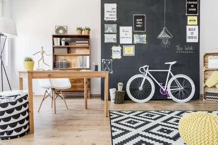 Nový designový byt s deskou ze zdi, motocyklem, stolem, židlí a detaily vzoru