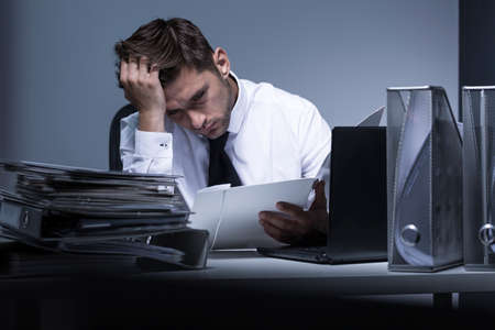 weary: Shot of a weary office worker sitting at a desk and running fingers through his hair