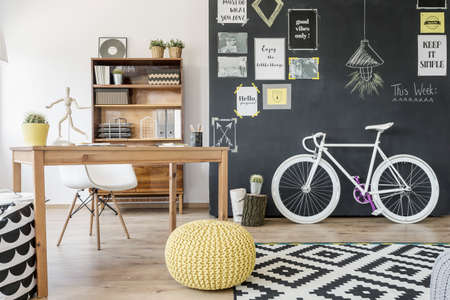 pouffe: Modern home space with chalkboard wall, bike, pouffe, pattern carpet, desk and chair
