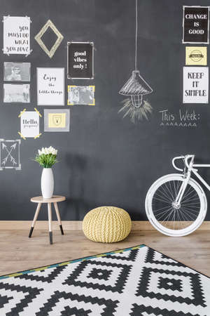 pouffe: Stylish and creative interior with blackboard wall, pattern carpet, bike, pouffe and decorative vase