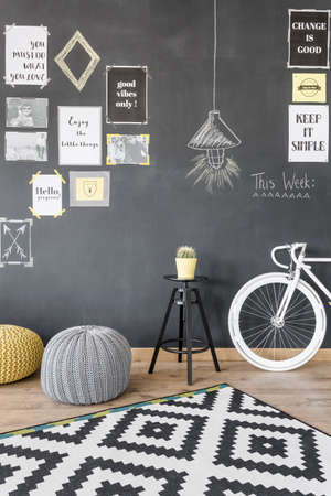 pouffe: Home interior with motivation blackboard wall, pattern carpet, modern pouffe and bike Stock Photo