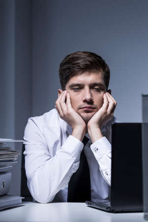 weary: Cropped shot of a weary businessman working overtime in his office