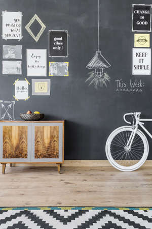 commode: New flat interior with blackboard wall, ethnic commode, bike and pattern carpet
