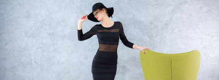 fashion clothing: Beautiful woman in black with a hat standing next to a green modern chair, panorama