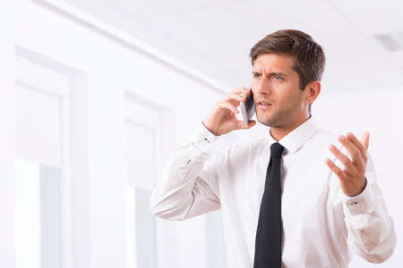 cropped shot: Cropped shot of an unhappy employee arguing with someone on the phone Stock Photo