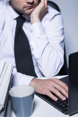 overwhelmed: Closeup of a overwhelmed businessman typing on a keyboard