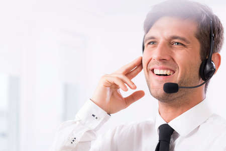 company job: Closeup of an attractive worker wearing a headset and smiling Stock Photo