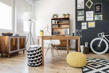 New style interior with ethnic commode, desk, chair, pouffe, bike and blackboard wall