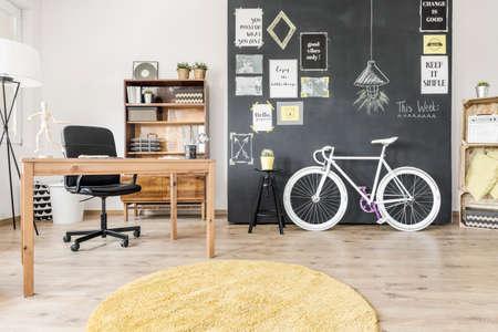 Interior de estilo criativo com mesa simples, cadeira, tapete redondo, bicicleta e parede de lousa Foto de archivo