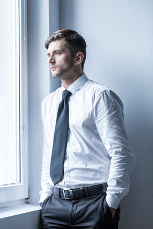 young businessman: Shot of a depressed businessman keeping hands in his pocket and looking through the window