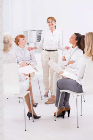 company job: Shot of a President of the Foundation smiling to her female associates Stock Photo