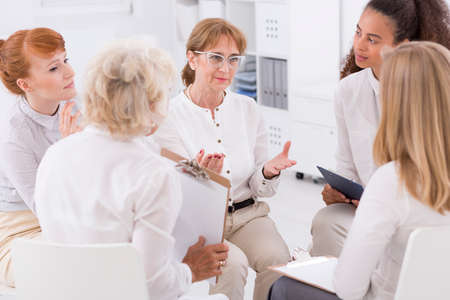 company job: Shot of beautiful businesswomen sitting in a circle and talking about their business
