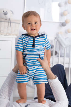 babysit: Shot of an unhappy baby boy standing on his fathers stomach