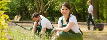 Shot van een gelukkig jonge tuinman lachend naar de camera en haar vrienden die werken in de achtergrond Stockfoto
