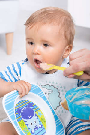 babysit: Closeup of a fathers hand spoon-feeding his sweet boy