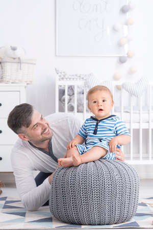 Shot of a father holding his baby boy sitting on a pouffe Stock Photo