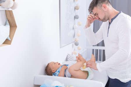 Foto de un padre disgustado tapar la nariz mientras se cambia un pañal