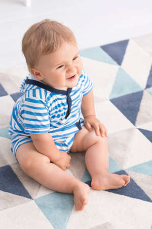Plan d'un petit bébé assis sur un plancher avec une grimace sur son visage