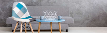 blue wall: Shot of a coffee table and a patchwork chair in a grey living room