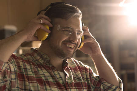 protective goggles: Smiling man in protective goggles assumes headphones