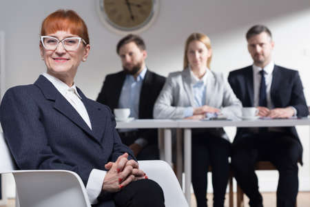 recruiters: Female job applicant is sitting on a chair and looking with satisfaction. At the background recruiters are looking at her Stock Photo