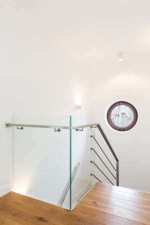 round window: Wooden staircase in a very modern house, with metal and glass rail and a round window in the hall