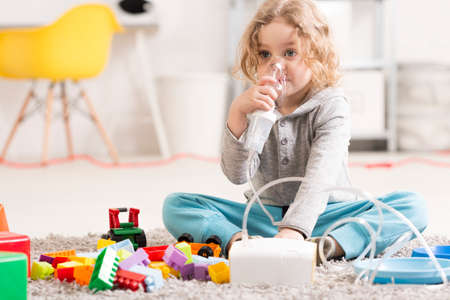 Little boy using an inhalator on the floor of his room, surrounded by toys Stock Photo